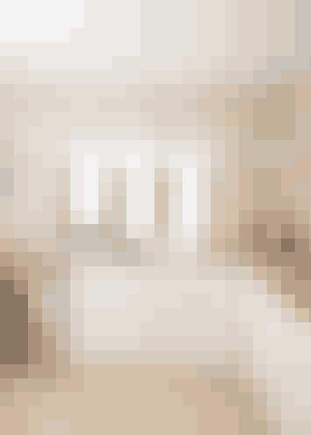 Hyggen er i højsædet i dette hvide IKEA-køkken.Lysekronen fra Ilva giver et behageligt lys,mens de indbyggede spots sørger for arbejdslys.De sandfarvede fliser matcher farven på væggen,der minder om kaffe med en god sjat mælk i.