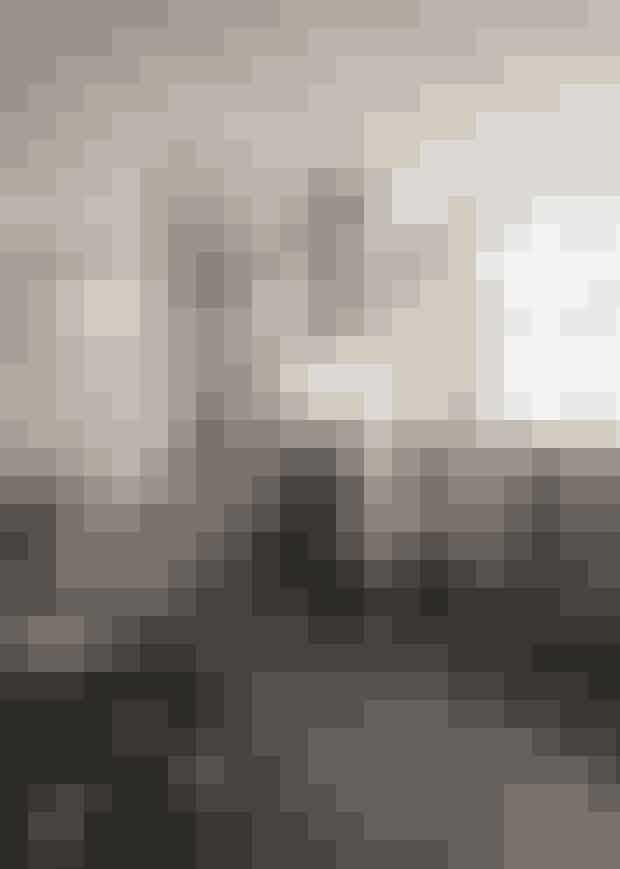 Køkkenetmed stålfronter er fra IKEA.Bemærk det sorte linoleumpå gulvet, der giver taktilitettil rummet. Selve bordpladener belagt med almindeligehvide 10 x 10 cm fliser.