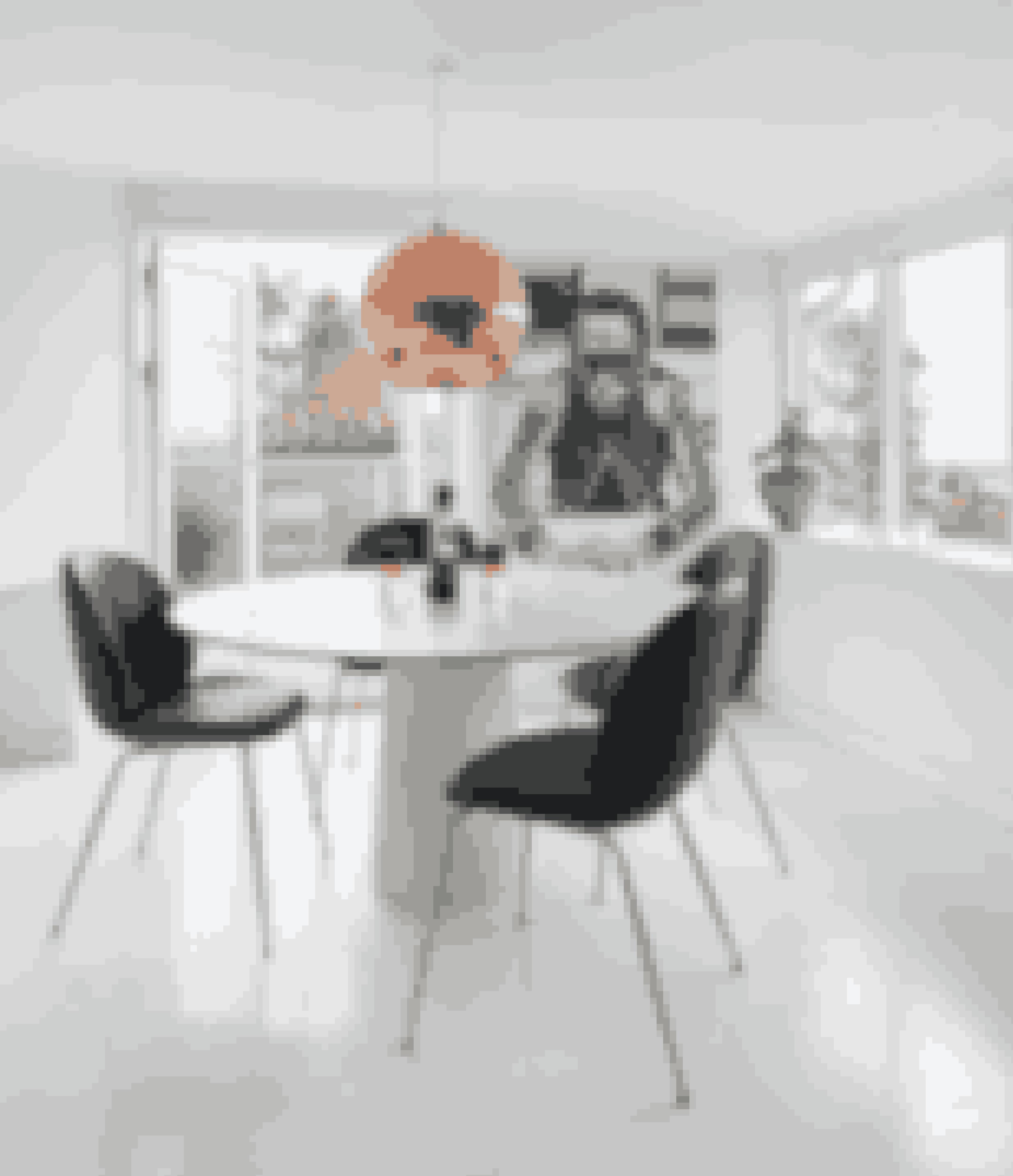 Spiseområdet er indrettet kontrastfyldt og med et strejf af eklektisk art deco. Gubi Beetle-stole er placeret omkring et rundt bord fra Moooi. Kobberpendel er designet af Tom Dixon, og lysestager i krystal er fra Reflections Copenhagen. På den bageste væg hænger et fotografi, som Julie har købt hos Modern Lamps. Krukken i vindueskarmen er fra De Fire Årstider.