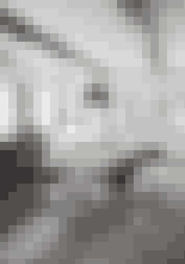 Leg med sort og hvidt som her, hvor familien har valgt at male loftbjælkerne med sort højglansmaling, der reflekterer lyset fra køkkenets mange vinduer. Køkkenet er fra Ikea. Spisebordet er fra Christiansen & Co. ligesom jernlysestagerne, tinkanden og lerkrukkerne. Vintagespisestolene Eames Arm Shell er købt hos Relove.dk, og den gamle Københavnerlampe er et loppefund.