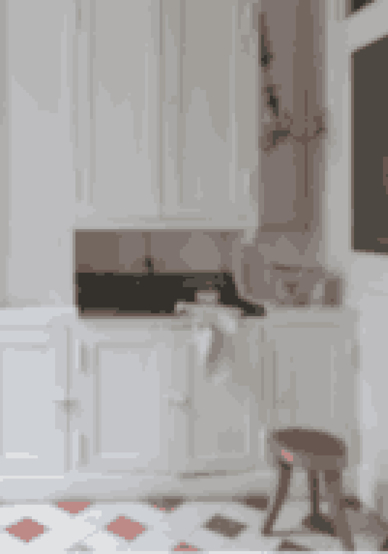 Hvis dit gamle køkken har elementer af god kvalitet, så bevar en sektion og mal den. De gamle hvide skabe og den store zinkvask får køkkenet til at fremstå som et fransk landkøkken, der er landet midt i Paris.