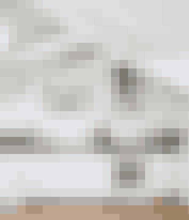 Selvom dette køkken kører et gennemgående hvidt tema, er der alligevel plads til lidt farver i form af pastelfarvede greb.