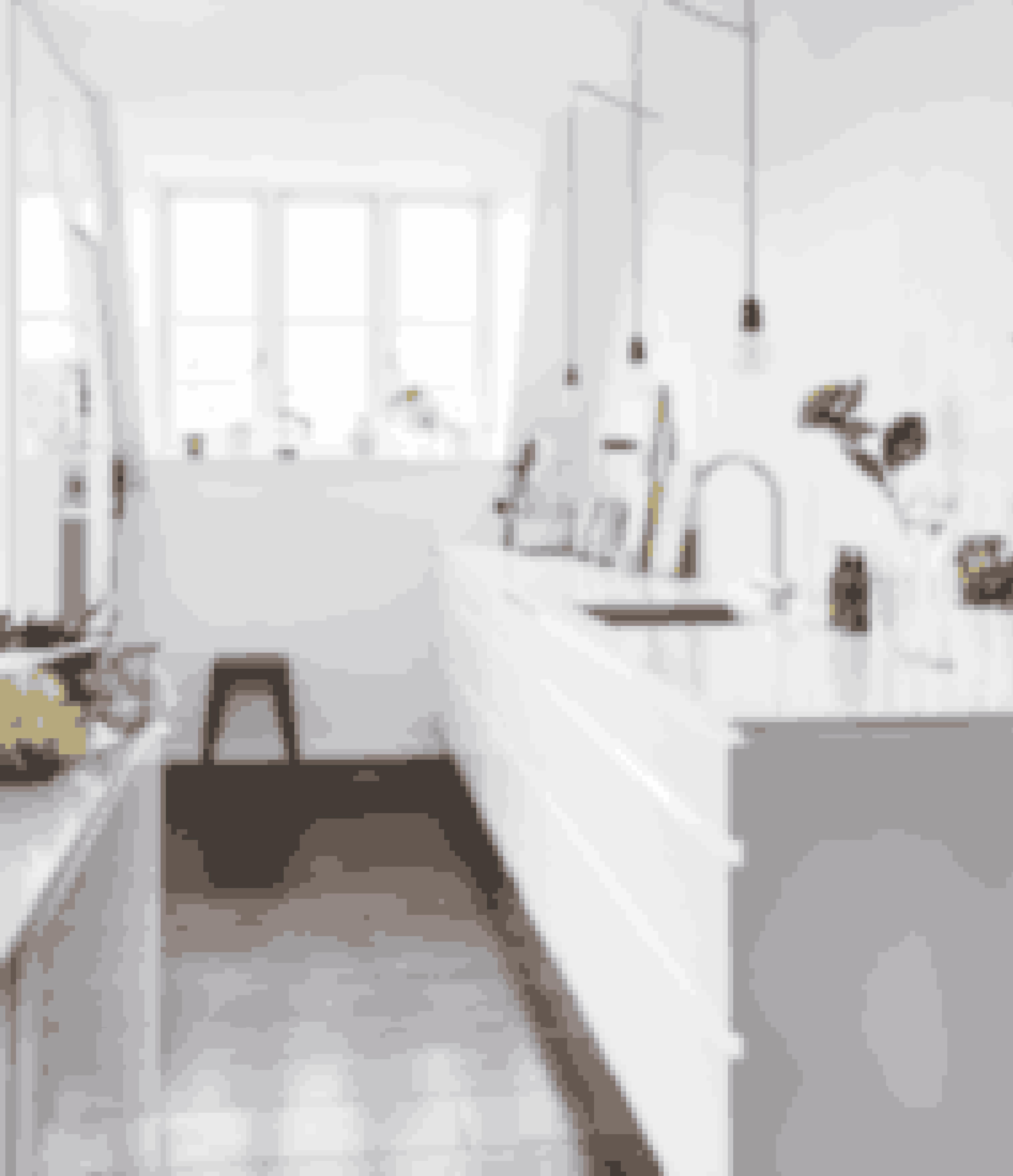 Hvid er en gennemgående farve i dette køkken, der bliver brudt op af små sorte detaljer, grønne planter og blomster.