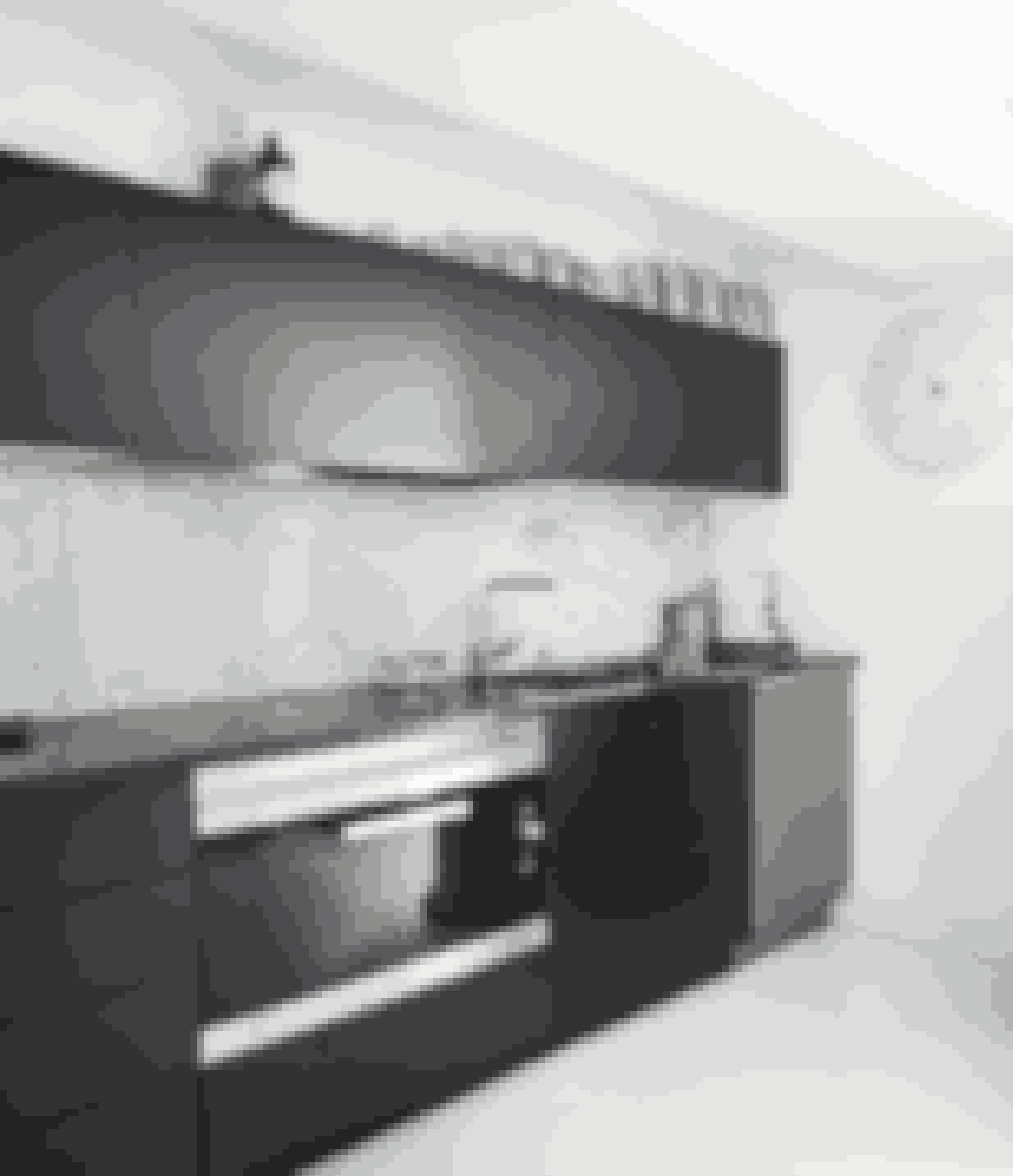 Den integrerede marmorvæg giver dette enkle og stilrene køkken et anderledes udtryk.