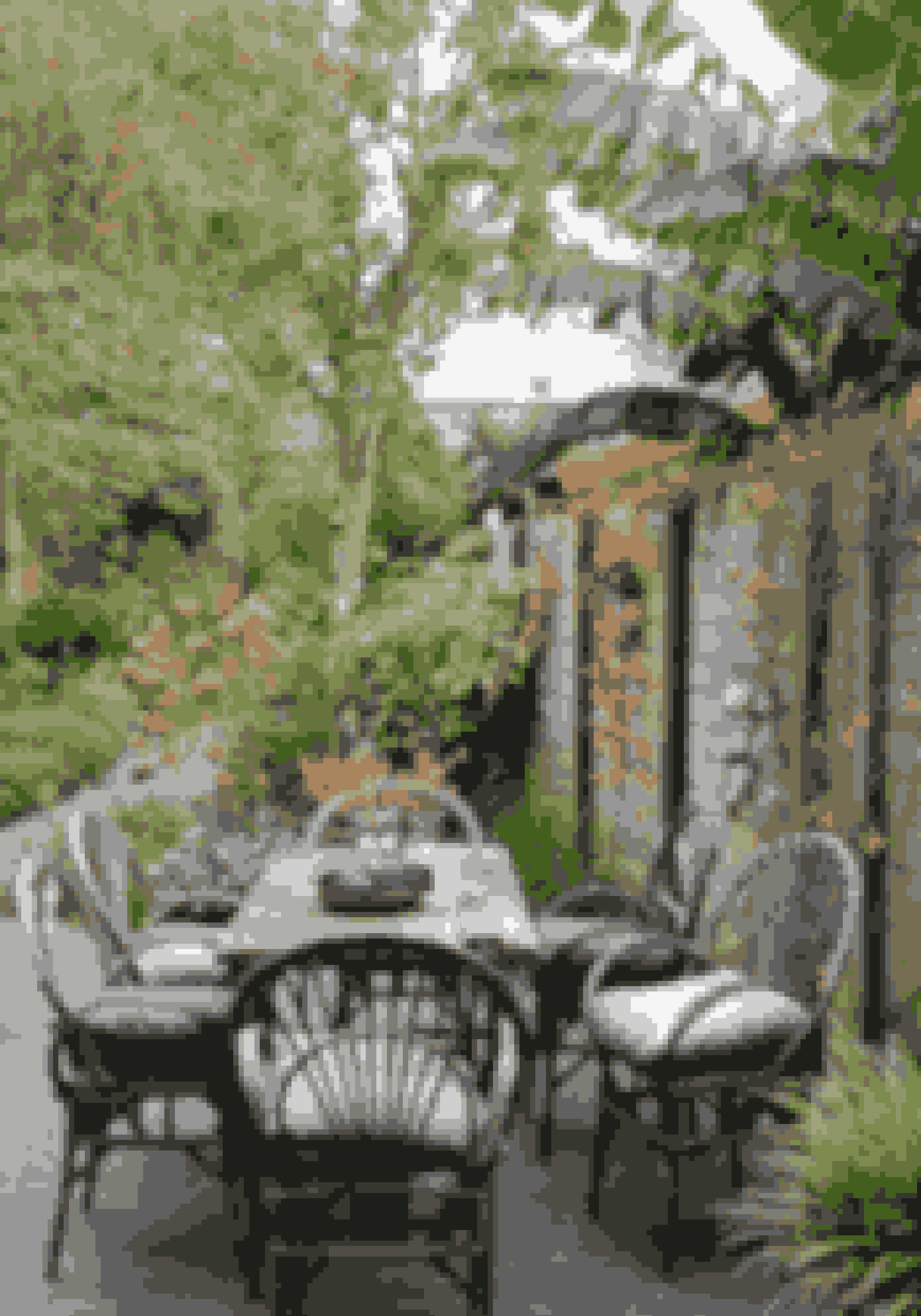 En have der næsten passer sig selv, med et rustikt spisebordssæt, giver en afslappet og hyggelig følelse, når du træder ud i haven.