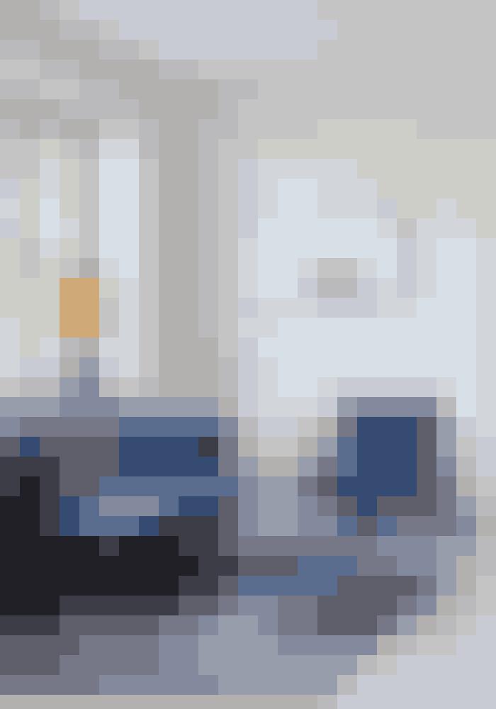Ligesom i spisestuen er opholdsstuen præget af den markante kongeblå farve på veloursofaen, stolen og sofabordet designet af Space Copenhagen for &tradition. Det blå tæppe under spisebordet er fra Lauritz.com. Billedet er en kunsttegning af Ene Bissenbakker Frederiksen, lampen i vindueskarmen er fra Rue Verte, og lysestagerne i messing er Nagel-stager.