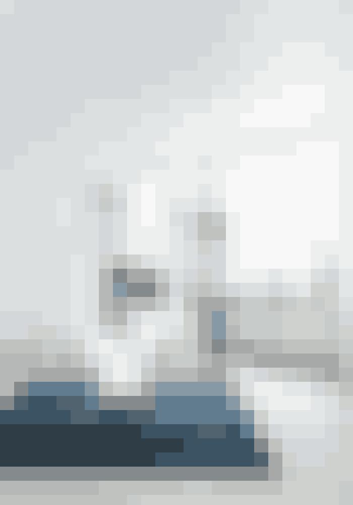 Bryd de store, hvide flader med farvede gulvtæpper. Det blå berbertæppe er købt i Casa Shop. Ellipsebordet, designet af Piet Hein, og Myrestolen, designet af Arne Jacobsen, købte Kirstine Harbou, da hun var 23 år, og de har nu opnået ikonstatus.