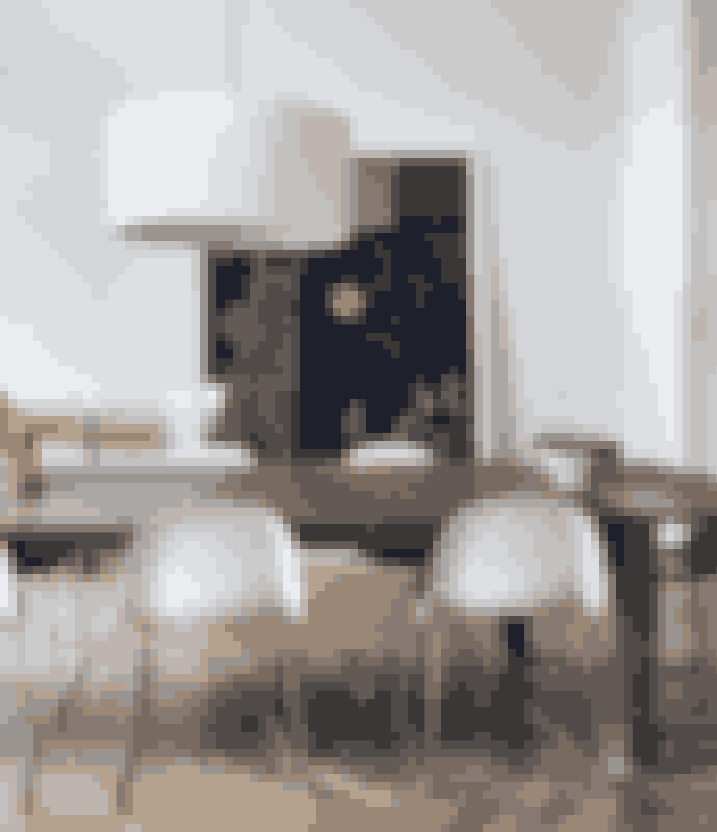 Skab kontraster ved at kombinere et rustikt langbord med strømlinede stole. En enkelt stor lampe er med til at give rummet herskabelighed. Langbordet, der er lavet af gamle døre fra Bali, er fra Campo & Co i Skodsborg, stolene er fra Gubi, og loftspendlen er fra Santa & Cole.