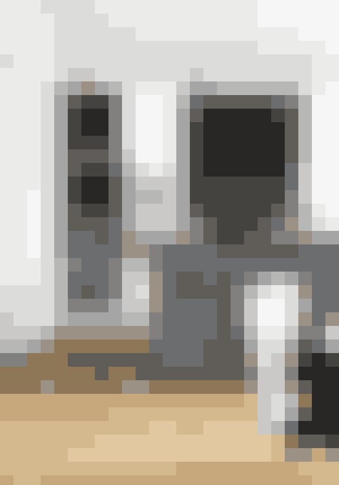 Leg med forskellige toner af træ − det skaber spil i de stilrene linjer i indretningen. Det store køkkenrum er indrettet af firmaet Simonsen og Czechura med specialdesignet emhætte, der matcher det mørke træ. Armaturet i bruneret messing er fra Quooker, lamperne er fra Møller og Rothe.