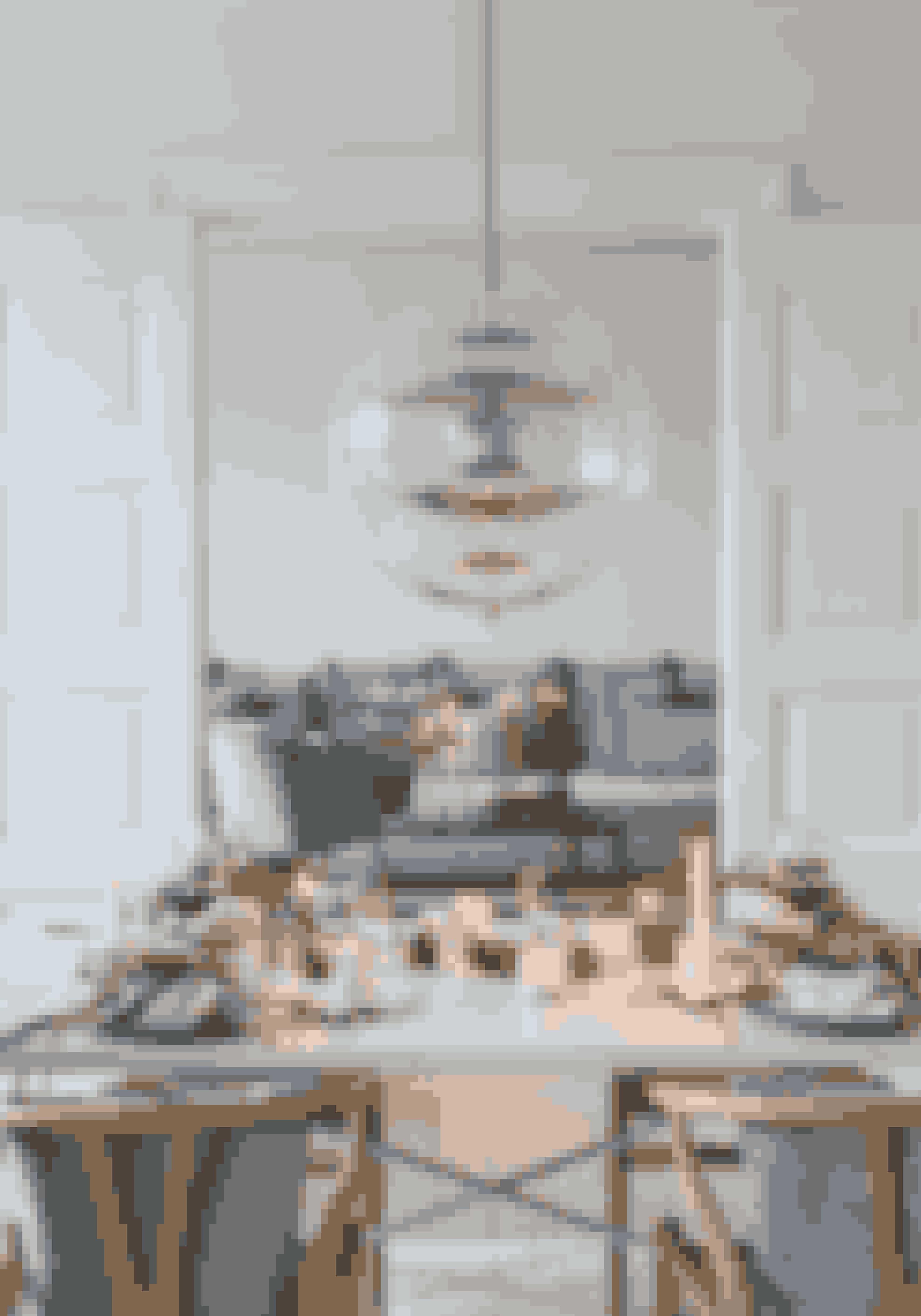 Stearinlys er stemningsgivere, og det kan være effektfuldt med mange i forskellige størrelser og farver sammen, bare de følger resten af farverne i pynten. Sofaen og marmorbordet er fra Bolia, og den grønne stol fra Søstrene Grene.