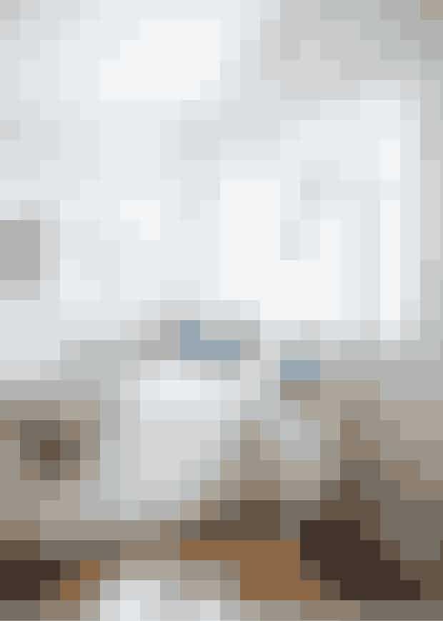 Hvidmalet træværk får sommerhusettil at fremstå lyst og roligt ogsåi soveværelset. Sengebordet oglampen er fundet på loppemarked,skindet er fra De Fire Årstider, denblå pude er fra Louise Roe og batikpudenfra House Doctor.