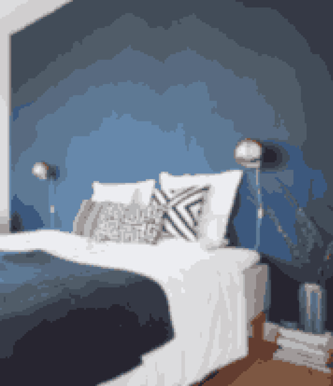 Mal hele bagvæggen i en kraftig farve i stedet for en sengegavl, hvis du vil have samme effekt med at ramme din seng ind, men gerne vil skifte udtryk lidt oftere. Blåt giver et køligt, roligt udtryk, mens de messingfarvede lamper giver lidt varme til rummet.