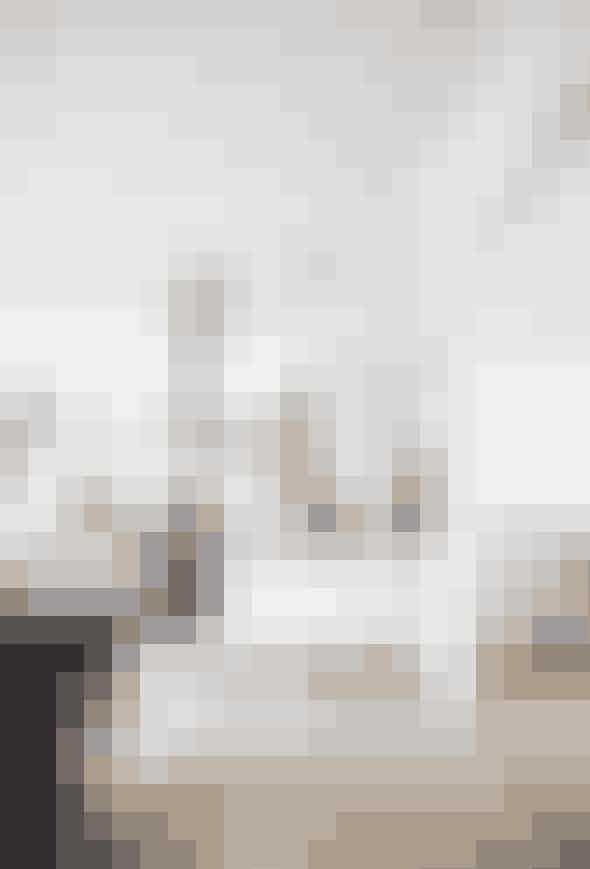 Selvom køkkeneter hvidt, er det ikkehelt hvidt. Parret harkombineret de hvidekøkkenelementermed den skulpturellehylde, mørke lamperog en markantø. Øen er bygget afbogkasser og maletmed grå Farrow &Ball-maling.Det asiatiske skrin,der bliver brugt tilbrød, er fra etloppemarked iSkotland. De sorteCaravaggio-lamperer designet afCecilie Manz forLight Years.