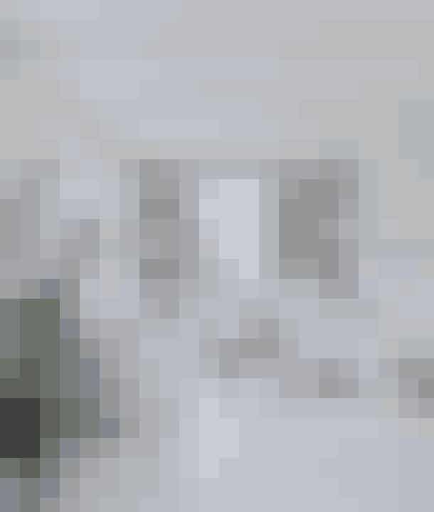 Lyse gulve uden tæpper får pejsestuen til at virke luftig, mens bløde puder, silkeskærme og synlige loftsbjælker understreger den afslappede og samtidig elegante stil. Sofabordet består af en planke, som Tine har købt på en rejse til Vietnam og fået bygget et understel til. Resten af interiøret er fra Tine K Home.