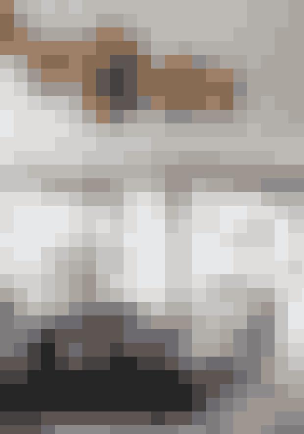 I stedet for at sætte sofaen op mod væggen kan du i stedet gøre den til rummets centrum og indrette rundt om den. Her er det en lædersofa fra 1950'erne, der står på et stort koskind. Klyngen af loftslamper hedder Melt og er designet af Tom Dixon.