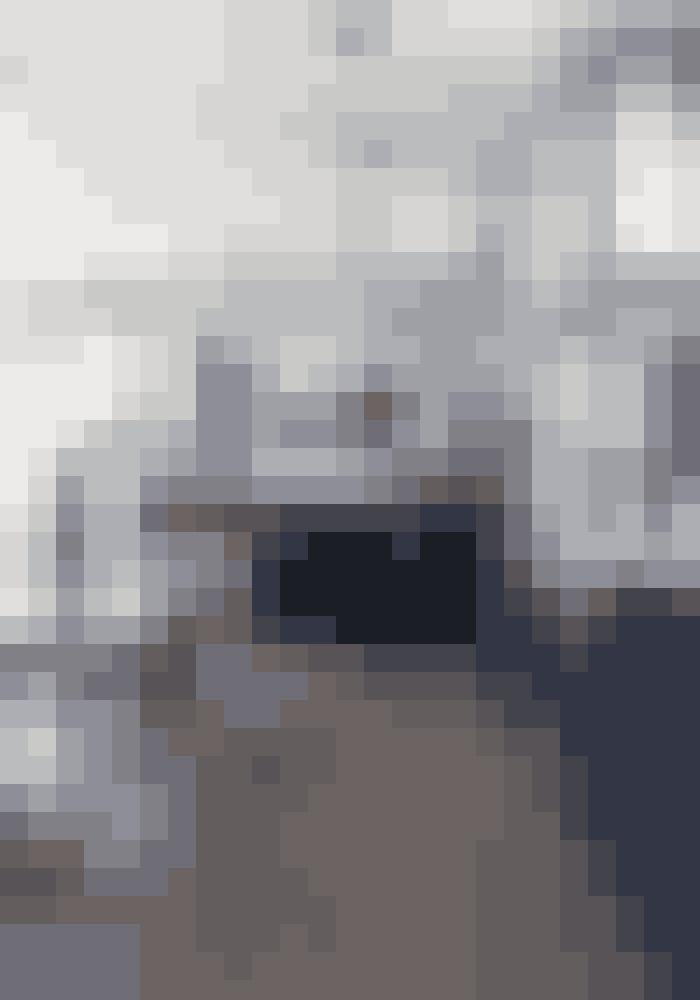 Hvis dit køkken er stort, så skab ro med gennemgående farver. Den forholdvis mørke egeparket spiller godt sammen med det mørkegrå snedkerkøkken og bordpladen i sort sten fra Zimbabwe. Selv det store antikke spejl har fået en ramme i en mørkegå nuance.