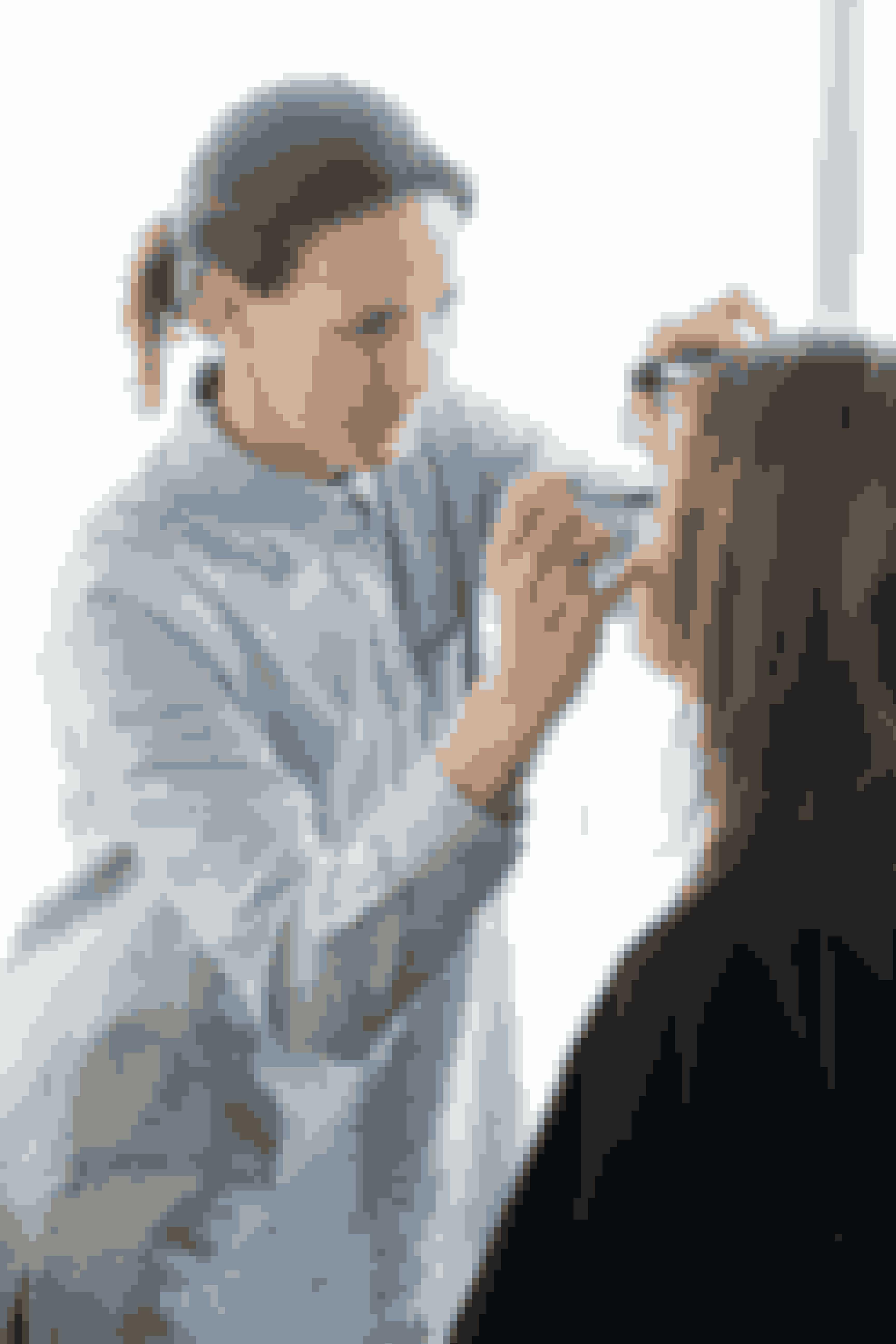 """Makeupartist Louise Trajano sørger for, at Karins hud er dejlig fugtig, inden hun begynder at putte makeup på. På den måde er det nemmere at lægge en god makeup. Hun begynder med at lægge foundation på huden for at give en god base at arbejde med. """"Karins hud er ret fin og uden dybe porer, så derfor undgår jeg bevidst at bruge en primer under huden,"""" fortæller Louise. Hun lægger lidt concealer under øjnene, som hun blander med creme, for at undgå at den bliver for tyk. På kinderne lægger Louise et tyndt lag pudder.På det yderste af øjenlåget og op til globelinjen lægger Louise en lilla øjenskygge. Ovenover lægger hun en mat, lys øjenskygge, som går op til brynet, og ved det inderste af øjet lægges en rosa øjenskygge med perlemor, som blendes sammen med den lilla øjenskygge. Den lilla øjenskygge lægges også under øjet for at indramme det. Afslutningsvis lægges en mascara, og læberne får lidt gloss."""